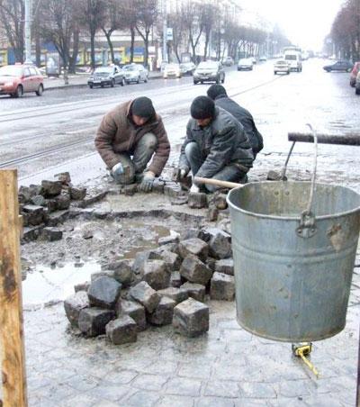 Працівники приватної фірми перекладають бруківку навпроти міськвиконкому у Вінниці