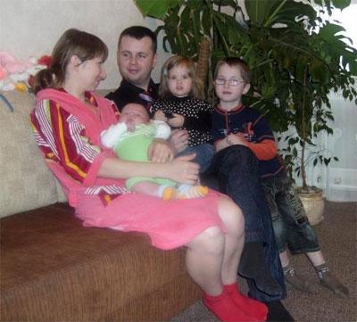 Сім'я дизайнера Олександра Очеретного у двокімнатній вінницькій квартирі. Дружина Марина тримає на руках чотиримісячного сина Данила, сидять старший Ілля та донька Єлизавета